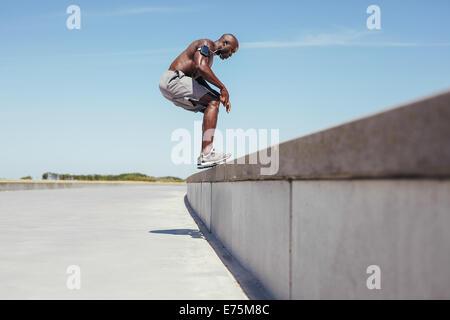 Bild von shirtless junge Sportler von der Wand springen. Afrikanische Fitness Männermodel Sprung Übung im Freien. - Stockfoto