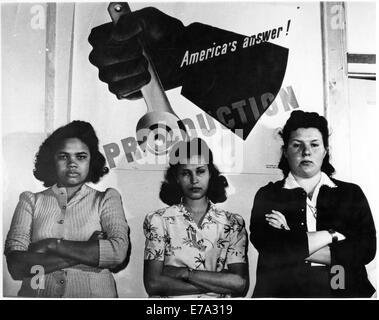 """Drei weibliche Fabrikarbeiter stehen vor """"Amerikas Antwort! Produktion """"Plakat während des zweiten Weltkriegs, circa - Stockfoto"""