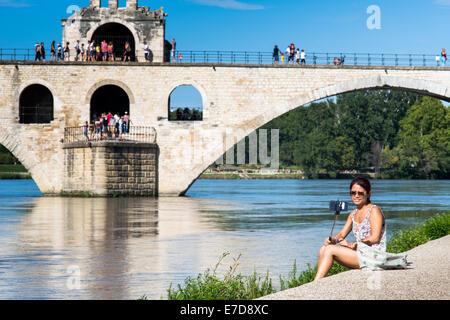 Junge Frau nehmen Selfie in der Nähe von Pont Saint-Bénézet Brücke über die Rhône, Avignon, Vaucluse, Frankreich - Stockfoto