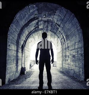 Junger Mann im dunklen Tunnel steht und schaut in das glühende Ende - Stockfoto