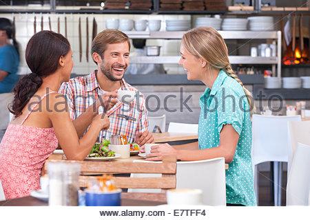 Lachenden Freunden Essen und trinken im restaurant - Stockfoto