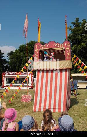 Kinder freuen sich über einen Punch & Judy show im Sandringham Flower Show, Norfolk, England. - Stockfoto
