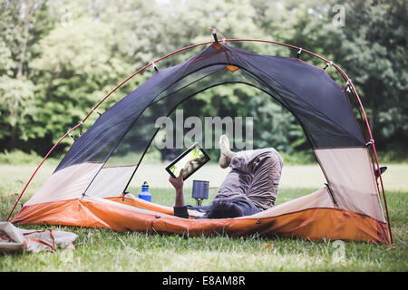 Reifer Mann liegen im Zelt mit digital-Tablette - Stockfoto
