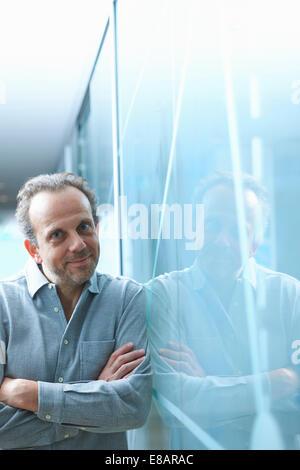 Zuversichtlich reifer Geschäftsmann gelehnt Glaswand im Büro - Stockfoto