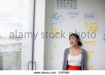 Lächelnde Geschäftsfrau mit vor Whiteboard mit Klebstoff Noten - Stockfoto