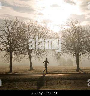 Silhouette einer Frau läuft durch den Park, England, UK - Stockfoto
