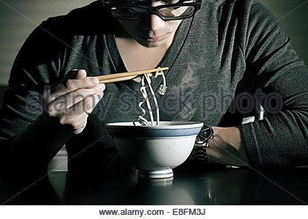 Mann isst konzeptionelle Nudeln - Stockfoto