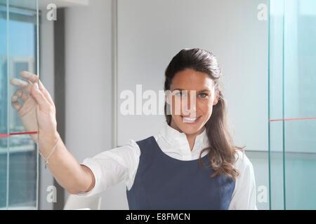 Porträt von lächelnden Geschäftsfrau, stehend im Büro vor whiteboard - Stockfoto
