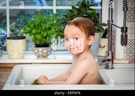 Jungen (2-3) unter Bad im Spülbecken - Stockfoto