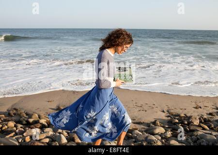 Frau mit Schreibmaschine Strand entlang spazieren - Stockfoto