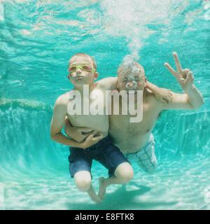 Porträt von Vater und Sohn unter Wasser in einem Schwimmbad - Stockfoto