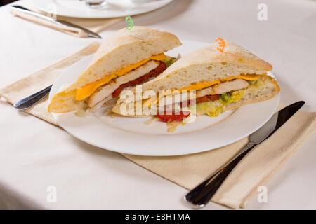 Vergoldete Sandwich serviert auf quadratischen Ciabatta Roll am Restaurant Gedeck - Stockfoto