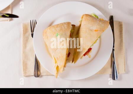 Aufwand für Sandwich auf quadratischen Ciabatta-Brötchen auf Platte im Restaurant Gedeck - Stockfoto