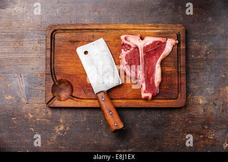 Rohes Frischfleisch t-Bone Steak und Fleischerbeil auf Schneidebrett auf dunklem Holz - Stockfoto