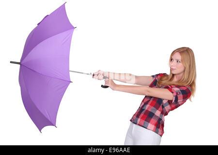 Frau und ihrem Schirm wird vom Wind weggefegt - Stockfoto