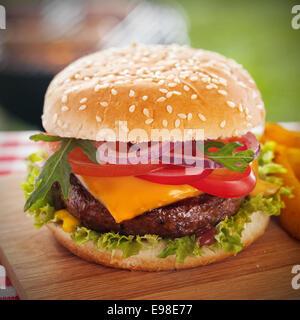 Leckere Burger mit Käse überbacken und einem dicken saftigen Boden Rindfleisch Patty, garniert mit Salat, Tomate, - Stockfoto