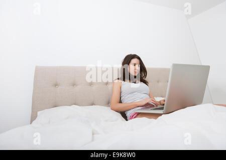 Junge Frau in Nachtwäsche mit Laptop im Bett - Stockfoto