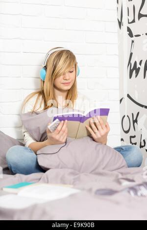 Teenager-Mädchen Musikhören während Lesebuch im Schlafzimmer in voller Länge - Stockfoto
