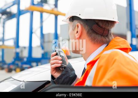 Mann mittleren Alters mit Walkie-talkie stehend neben Auto im Frachthafen - Stockfoto