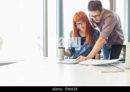 Geschäftsleute, die Datei gemeinsam am Schalter in Kreativbüro analysiert - Stockfoto