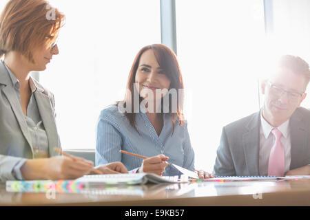 Lächelnde Geschäftsfrau mit Kollegen im Tagungsraum - Stockfoto