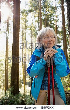 Heitere senior Frau Wandern im sonnigen Wald - Stockfoto