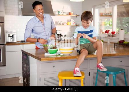 Vater und Sohn in Küche, junge sitzt an Theke - Stockfoto