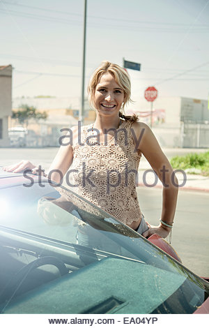 Porträt der jungen Frau, die neben dem Auto stand - Stockfoto