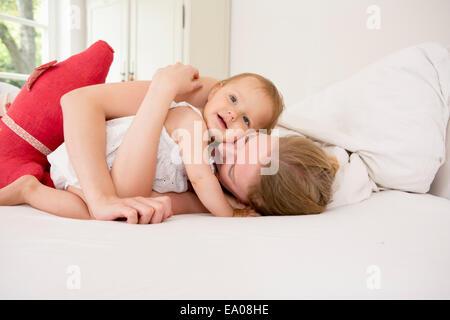 Mutter umarmt Baby-Tochter auf Bett - Stockfoto