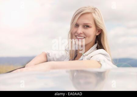 Junge Frau lächelnd neben Auto - Stockfoto