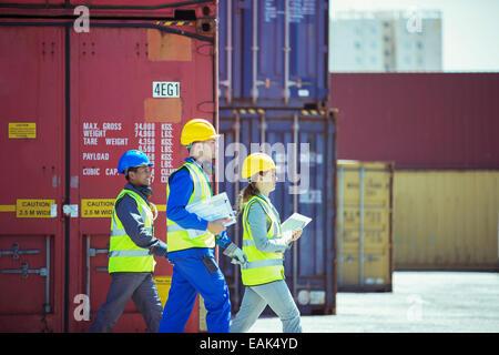Geschäftsleute und Arbeiter zu Fuß in der Nähe von Containern - Stockfoto