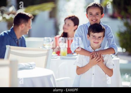 Porträt des Lächelns Bruder und Schwester, Eltern sitzen am Tisch im Hintergrund - Stockfoto