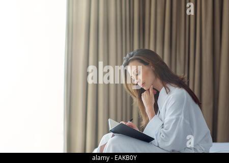 Nachdenkliche Frau mit weißen Bademantel schreiben im Editor im Schlafzimmer - Stockfoto