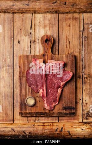 Rohes Frischfleisch t-Bone Steak und Gewicht auf Schneidebrett auf hölzernen Hintergrund - Stockfoto