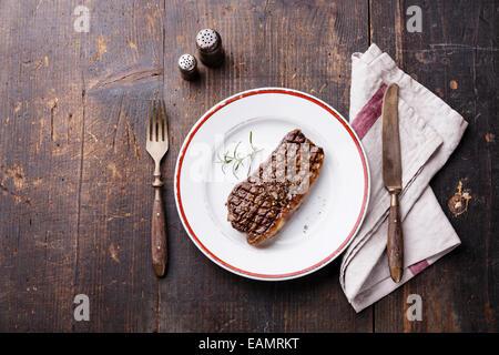 Striploin Steak auf dem Teller und Gabel und Messer auf Holz Hintergrund - Stockfoto