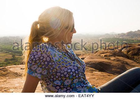 Eine Mädchen entspannt in der Sonne auf den Felsen rund um Hampi - Stockfoto