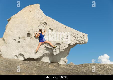 Frankreich, Korsika, junge Frau, die großen Felsen klettern - Stockfoto