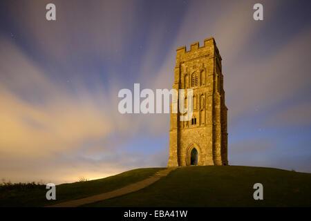 Glastonbury Tor, Somerset, beleuchtet durch das warme Glühen der Straße Beleuchtung aus der nahe gelegenen Stadt - Stockfoto
