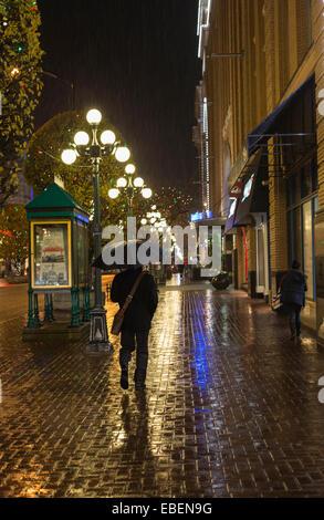 Mann zu Fuß in der Innenstadt von Victoria auf regnerischen Nacht-Victoria, British Columbia, Kanada. - Stockfoto