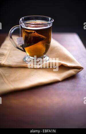 Eine Tasse heißer schwarzer Tee auf einem gelben Leinen und dunklen Oberfläche des Holzes. Dunklen Morgen fühlen. - Stockfoto