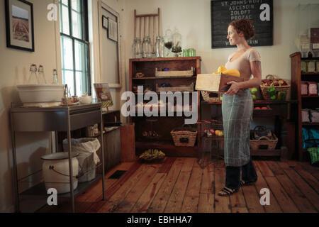 Weibliche Verkäuferin mit Obst und Gemüse Kiste im Dorfladen - Stockfoto