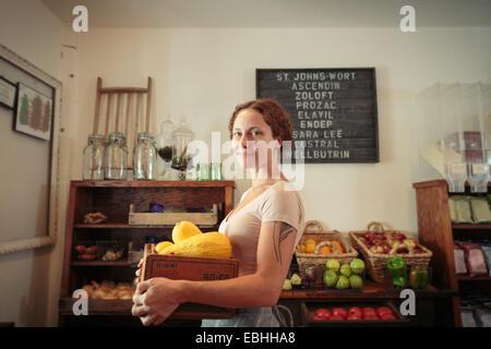 Porträt von weiblichen Verkäuferin mit Obst und Gemüse Kiste im Dorfladen - Stockfoto