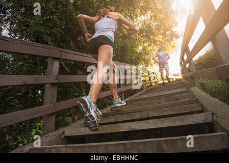 Mitte erwachsenen Mann und junge Frau angerannt Schritte, hinten, niedrigen Winkel Ansicht - Stockfoto