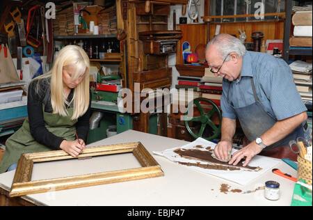 Ältere Mann und junge Frau, die Wiederherstellung Bild Rahmen und Buch Wirbelsäule in traditionellen Buchbinderei - Stockfoto