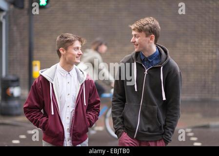 Zwei männliche Freunde, die Straße überqueren - Stockfoto