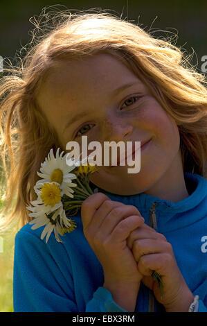 Porträt einer lächelnden 8-jähriges Mädchen mit einem Haufen von Gänseblümchen in der Hand, Frankreich - Stockfoto