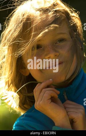 Porträt einer lächelnden 8-jähriges Mädchen mit den Haaren mit ihren Haaren und ein Gänseblümchen in ihrer Hand - Stockfoto