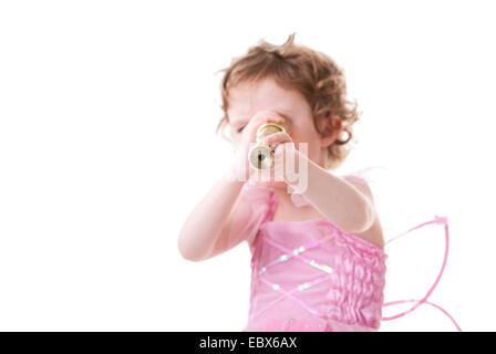 Niedliche lockige Mädchenakt in kleinen Fee Kleid suchen, Teleskop - Stockfoto