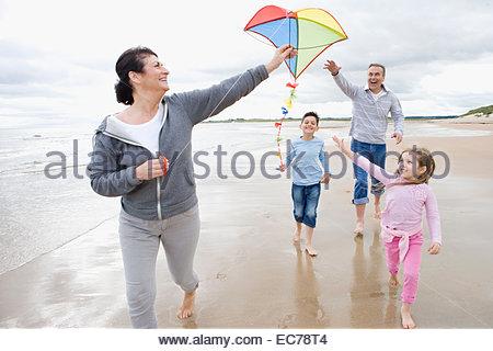 Großeltern und Enkel fliegen Kite am Strand - Stockfoto