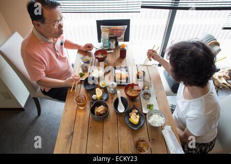 Frau und Mann sitzt an einem Tisch, japanisches Essen mit Stäbchen zu essen. - Stockfoto